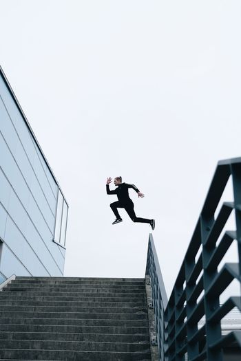 Low angle view of man jumping on staircase against clear sky