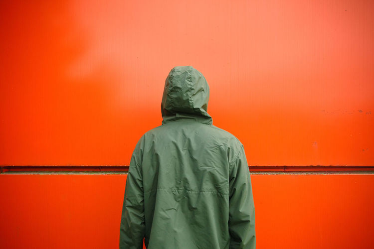 Anonymity Anonymous Autumn Back Façade Green Color Wall Abstract Architecture Autumn🍁🍁🍁 Camouflage Contrast Contrasting Colors Copy Space Looking Mysterious Orange Color Raincoat Rear View Red Standing Unrecognizable Person Waist Up Wall - Building Feature