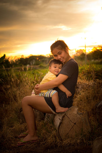 Portrait of happy mother and son on field against sky during sunset