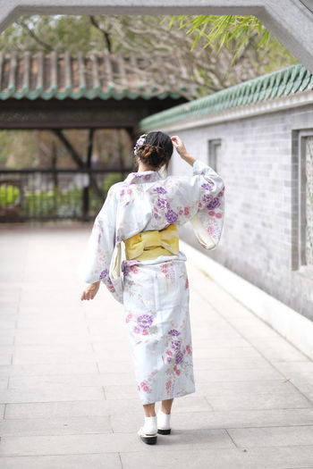 Rear view of woman wearing kimono while walking by house