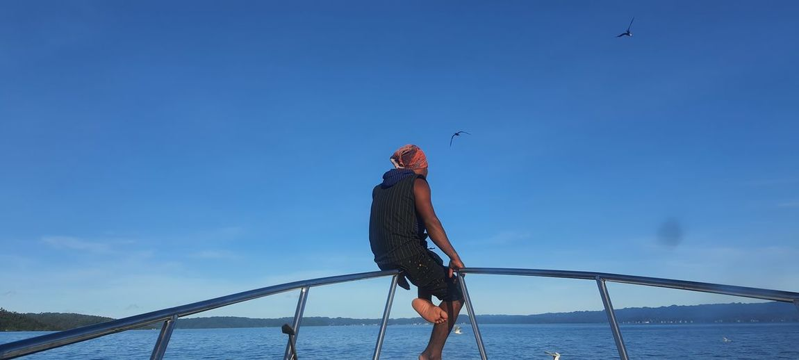 Man standing by sea against blue sky