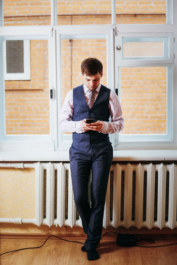 Full length of young man using phone while standing on building