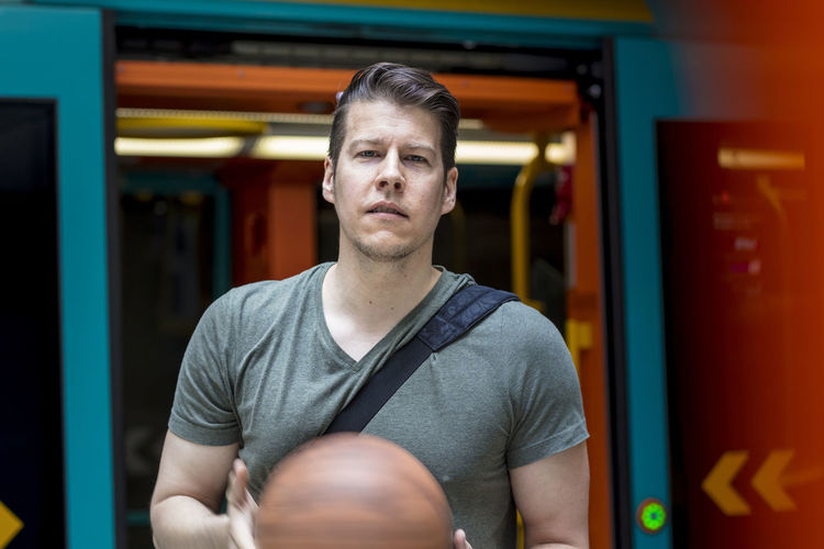 Portrait Of Young Man With Basketball Standing At Train Entrance