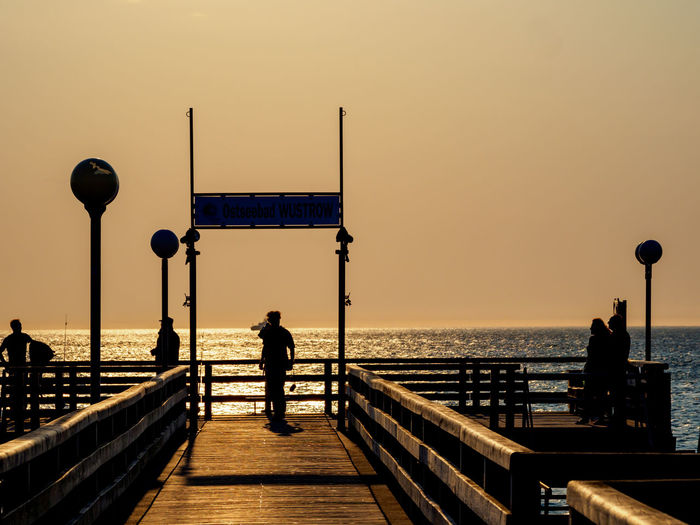 Silhouette man standing on railing against sea during sunset