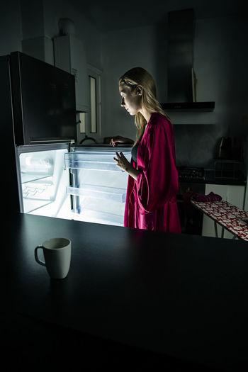 Side view of woman opening refrigerator door in kitchen