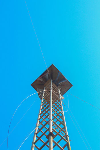 Low angle view of lookout tower against clear blue sky