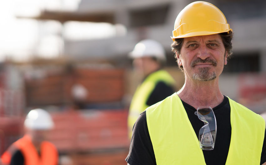 Portrait Of Engineer Wearing Hardhat At Construction Site