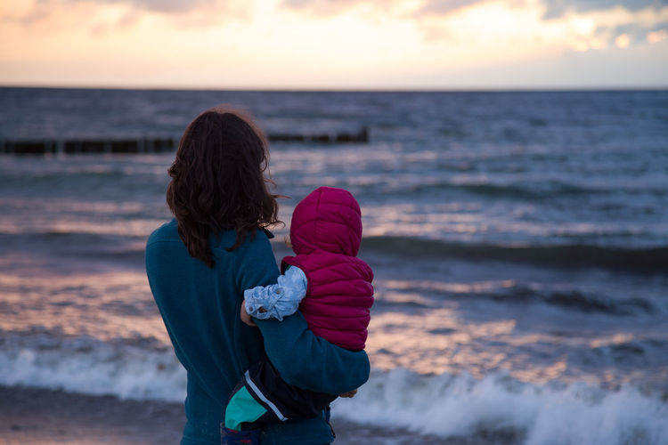 Young woman and hery baby are watching the sunset above the Baltic Sea near Rostock, Germany Baby Baltic Sea Beach Beauty In Nature Child Horizon Over Water Leisure Activity Lifestyles Nature One Person Outdoors Real People Sea Sky Sunset Tranquility Water Women Young Women