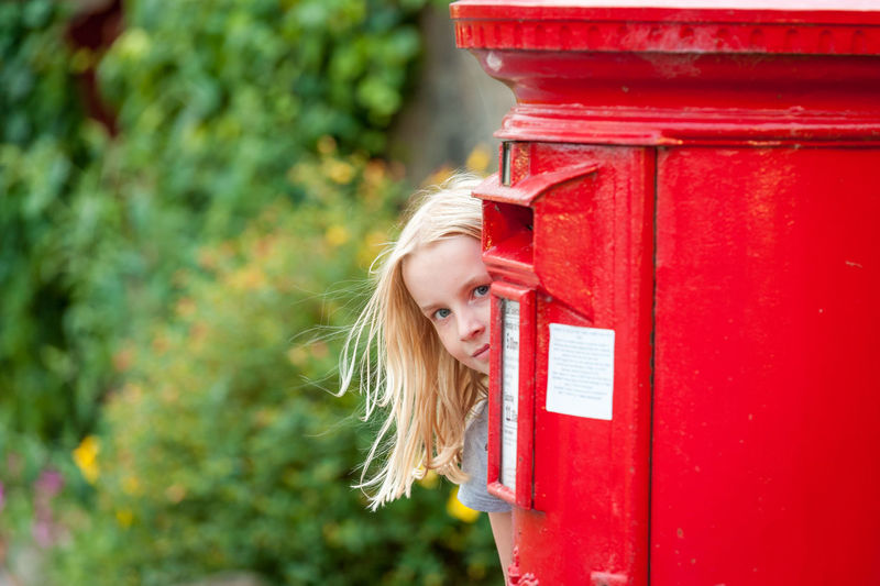 Portrait of girl peeking behind red mailbox