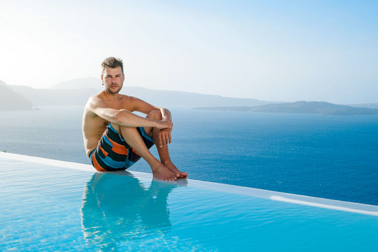 Portrait of handsome man by swimming pool against sea