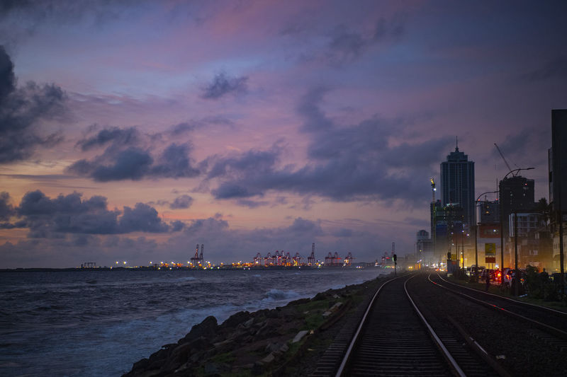 Railroad tracks in city against sky at sunset