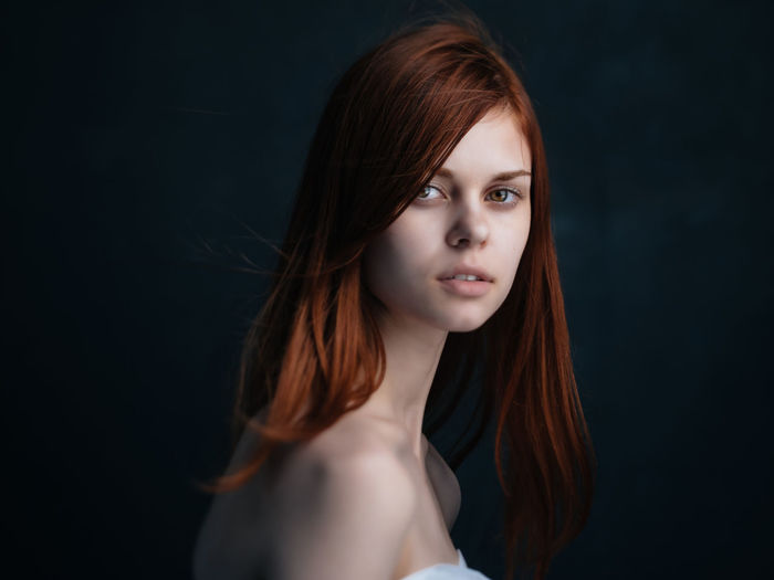 Portrait of beautiful young woman against black background