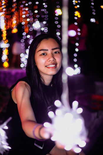 Portrait of smiling young woman holding illuminated string lights at night