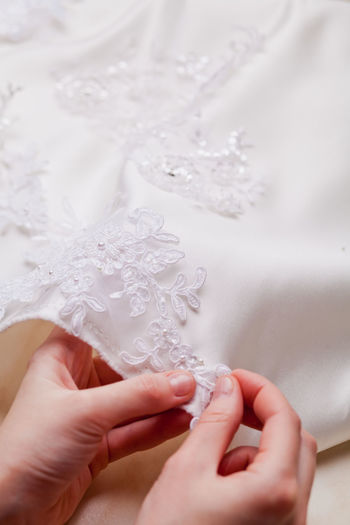 Close-up of hand sewing lace on wedding dress
