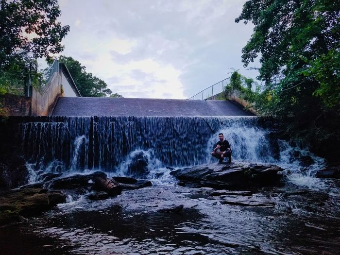 Man surfing in waterfall against sky