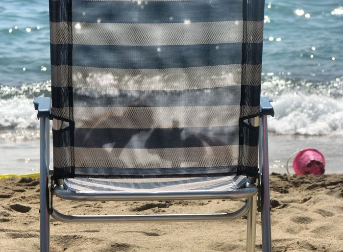 Close-up of deck chairs on beach