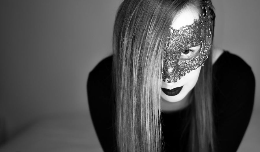 Close-Up Portrait Of Young Woman Wearing Mask While Standing Against Wall