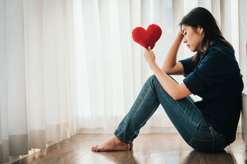 Side view of woman holding heart shape sitting at home