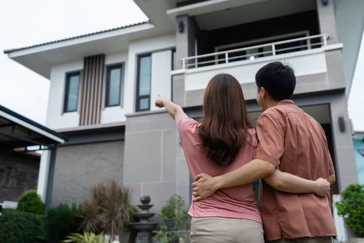 Rear view of couple standing outside building