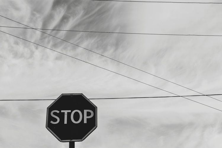 Low angle view of stop sign against sky