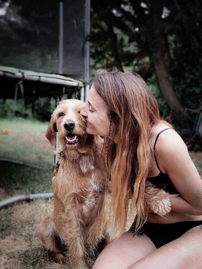 Woman with dog sitting outdoors
