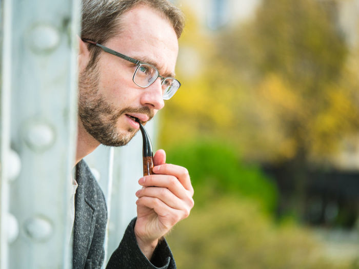 Mid Adult Man Looking Away While Smoking Outdoors