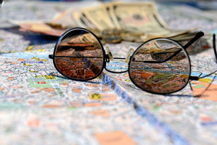 Sunglasses and money on a tourist map background. Tourism concept. Dollar Money Cash Savings Banking Finance Bill Currency Wealth Background Banknote Bussiness Profit Green Close-up USD Exchange Loan  Paper Sign Payment Pay Stack Number Textured  Abstract Earnings Symbol Capital Assets Sunglasses Map Tourism Euro Coins Travel Destination Concept Glasses Selective Focus Eyeglasses  No People Direction Guidance Still Life Discovery Outdoors World Map Lost Antique Journey Choice Exploration