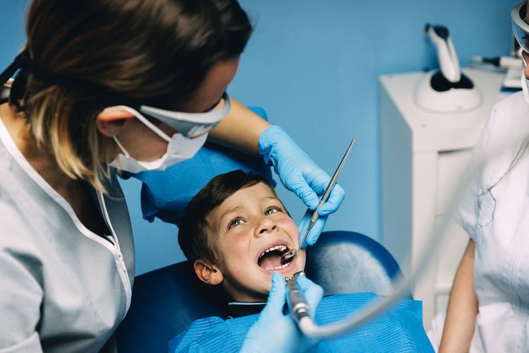 Dentists Examining Boy In Clinic