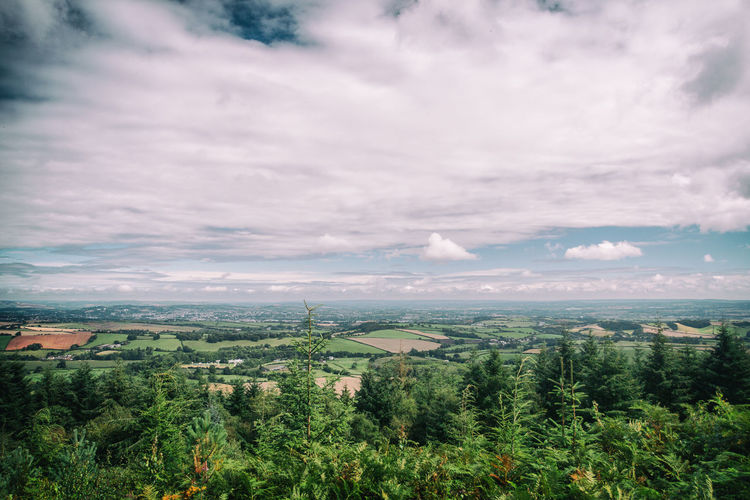 Scenic view of green landscape against cloudy sky