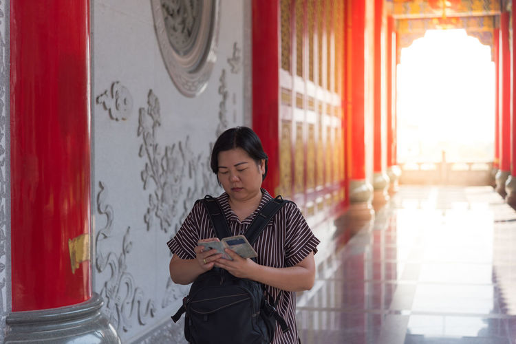 Mature woman using phone while walking in shrine