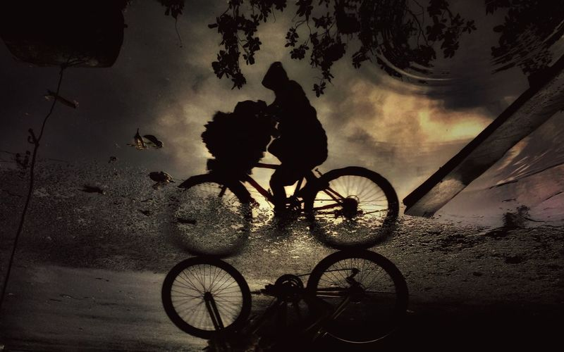 Reflection Of Silhouette Person Cycling By Puddle On Footpath During Sunset