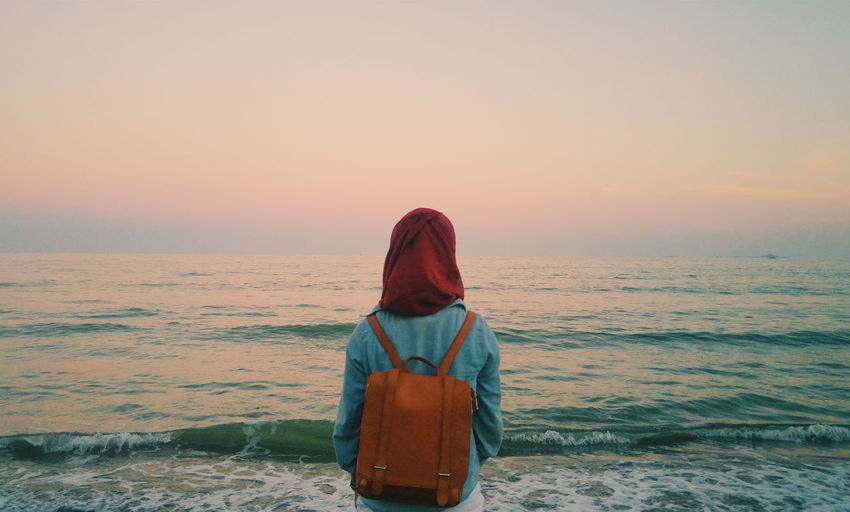 Rear view of woman carrying backpack standing at sea shore during sunset
