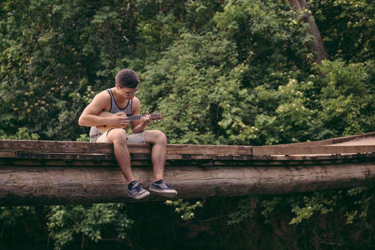 Young Man Playing Ukulele On Footbridge