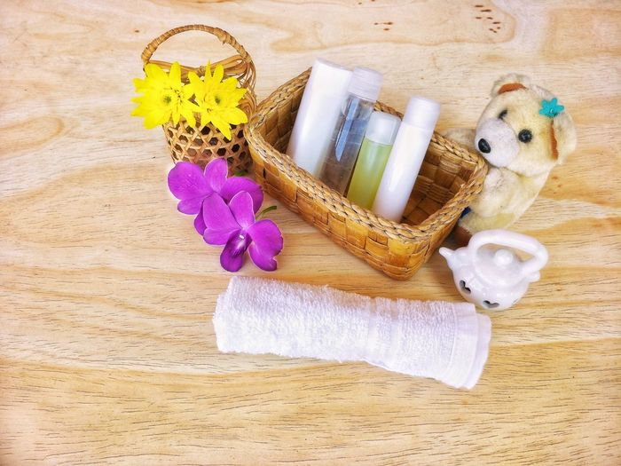 The arrangement of bathroom setting in wooden basket on wooden table in interior decorations concept Bear Basket Interior Arrangement Health Kin Bathroom Setting Orchid Chrysanthemum Purple Yellow Brown Soap Shampoo Teddy Doll Decoration Spa Home House EyeEm Selects High Angle View No People Indoors  Day Close-up Freshness Directly Above