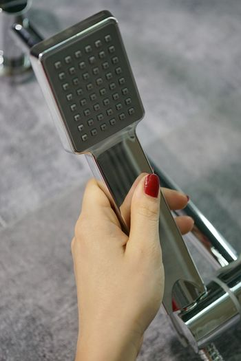 Close-up of woman holding shower faucet