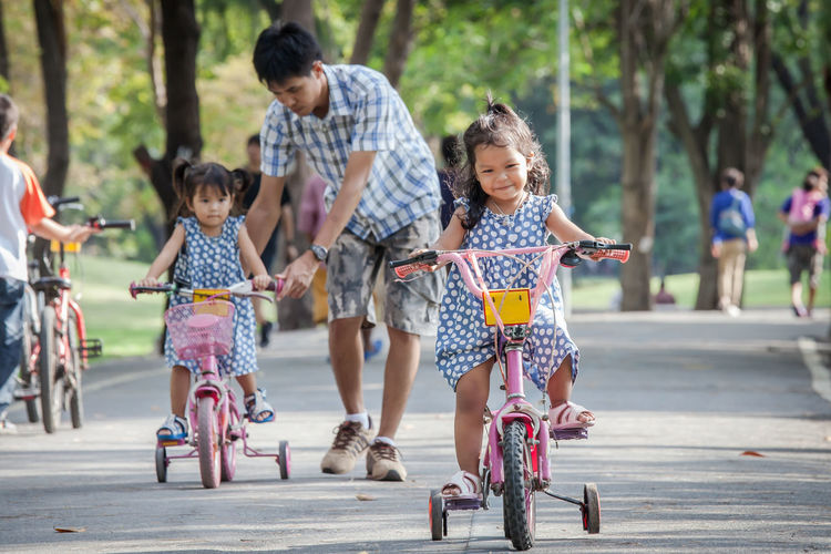 Full Length Of Sisters Riding Bicycles With Father On Road At Public Park