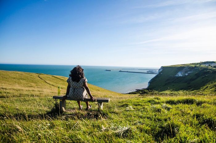 Woman sitting on a bench at the White Cliffs of Dover overlooking the port and the English Channel in Kent, England. Mature Woman Woman Woman Sitting On Bench Sitting Relaxing Bench White Cliffs Of Dover Dover Port Of Dover Kent Coast England Relaxation English Channel Sea Sky And Clouds Summer Landscape Rural Countryside Nature Rest England Uk Tranquility Breathing Space Investing In Quality Of Life Second Acts