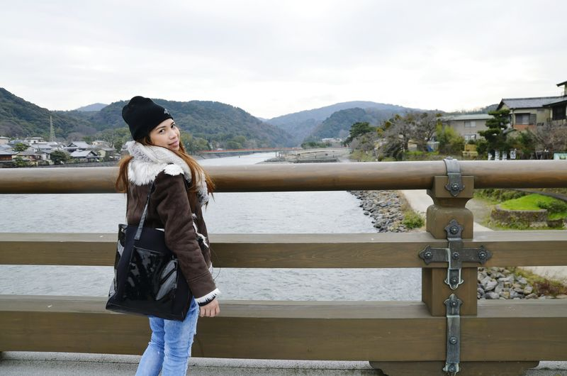 Portrait of young woman standing on railing against river