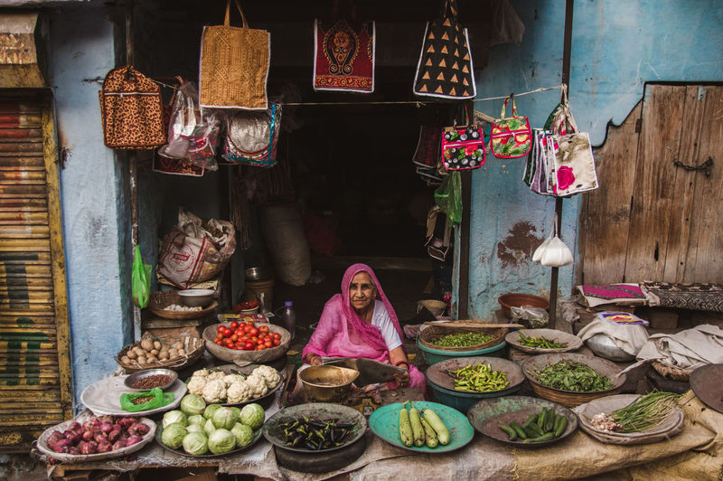 A vegetable shopkeeper in the blue streets of Jodhpur. She was all smiles when I approached to take a photo of her. This is the case with teh entire blue city of Jodhpur. People are very kind and welcoming towards the travellers and they're proud of their city. Jodhpur is also known as the Blue heaven , which I can never object. Travel Streetphotography Cultures Local Shopkeeper Shop Vegetable Woman Mature Adult Adult Grandma Jodhpur Rajasthan Blue Storytelling Smiling Market Stall Tart - Dessert Fruit Sweet Pie Basket Variation Flower Food And Drink Street Market For Sale Farmer's Market Raw Retail Display The Photojournalist - 2019 EyeEm Awards The Traveler - 2019 EyeEm Awards The Street Photographer - 2019 EyeEm Awards