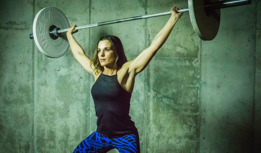 Beautiful Woman Lifting Barbell Against Wall