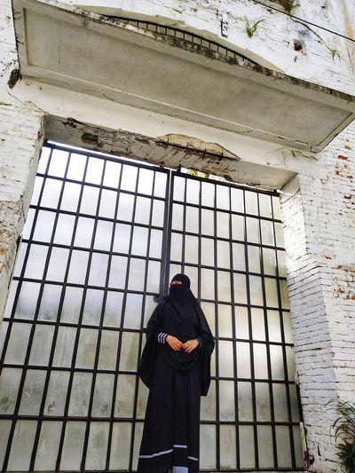 Woman wearing black hijab standing against gate