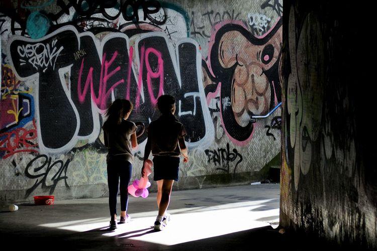 People walking in graffiti on wall