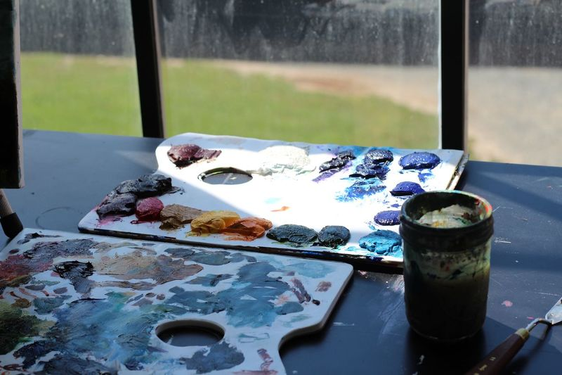 painters necessities Brush Color Day Light No People Painting Pallete Sun Table Still Life Paintbrush Close-up Messy Outdoors Palette Plate Nature Freshness High Angle View Art And Craft Sunlight Focus On Foreground Glass - Material