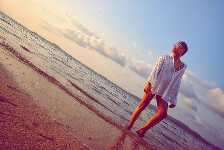 Low Angle View Of Young Woman Standing At Beach Against Sky During Sunset