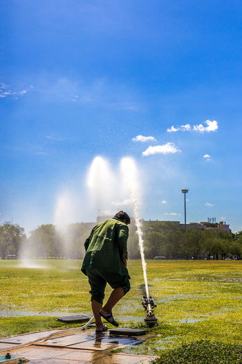 A workman is sprinkle water on grass in the Phra Meru Ground in Bangkok Activity; Arena; Bangkok; Blue Sky; Ceremony; Cheerful; Cloud; Culture; Day; Environment; Field; Freedom; Grass; Green; Ground; Happiness; Jogging; Kite; Meadow; Outdoor; Phra Meru Ground; Religion; Sprinkle; Thailand; Tradition;