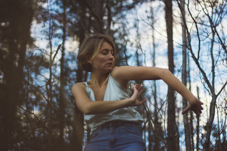 Low angle view of young woman dancing in forest