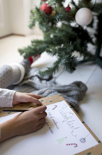 Cropped image of girl writing on paper by christmas tree at home
