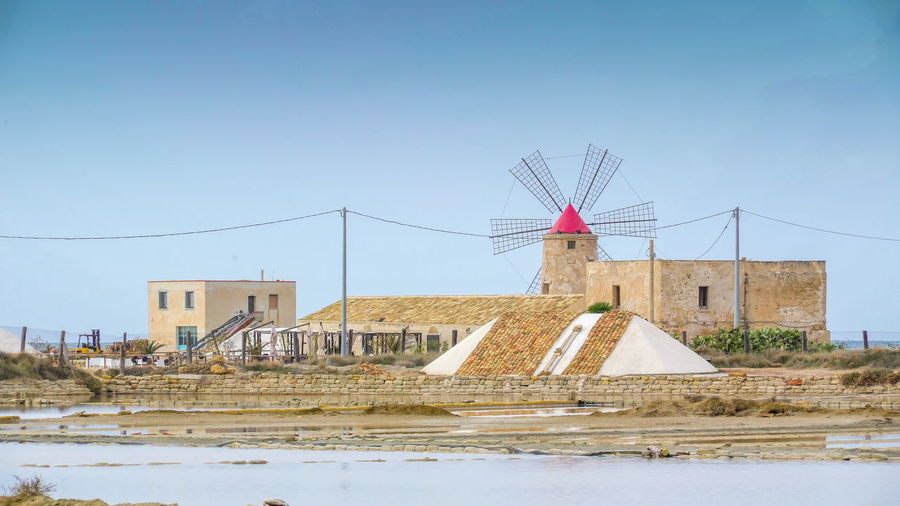 Traditional windmill by building against clear sky