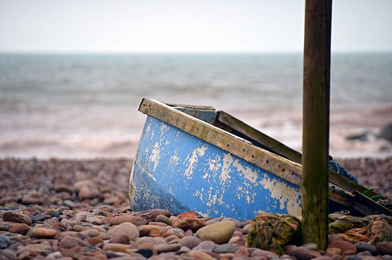 Close-up of abandoned boat on beach against sky