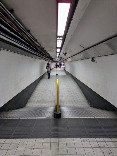 Man in illuminated underground walkway